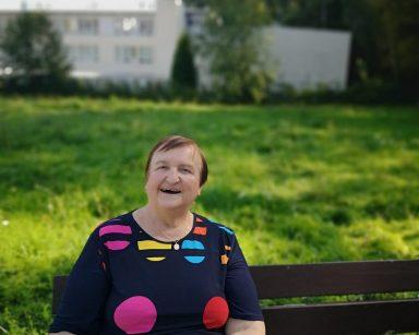 Roześmiana seniorka na ławce. W dłoni trzyma kubek. Za nią pas zielonej trawy i budynek DPS.
