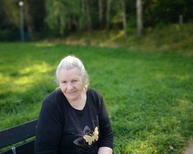 Uśmiechnięta seniorka na ławce. W dłoniach trzyma kubek. Za nią zielona trawa i drzewa.