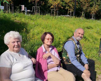 Troje seniorów na ławce. Uśmiechają się o mrużą oczy od słońca. Za nimi zielona trawa, siłownia zewnętrzna, las.