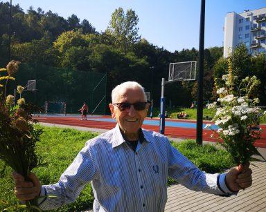 Roześmiany senior w przeciwsłonecznych okularach. W dłoniach trzyma wielkie bukiety polnych kwiatów. W tle boisko.