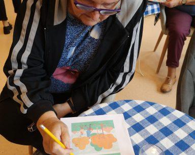 Seniorka siedzi przy stoliku. Nachyla się nad kartką z ćwiczeniami. W dłoni trzyma długopis.
