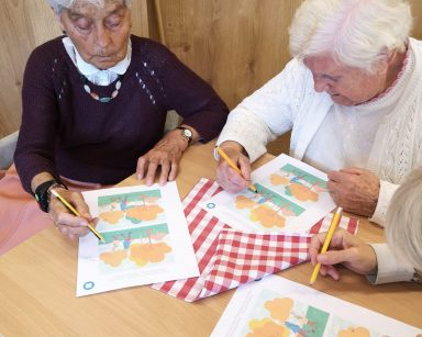 Seniorki przy stoliku. Rozwiązują ćwiczenia na kartkach.