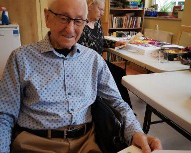 Senior siedzi uśmiechnięty. W dłoni trzyma kartkę z ćwiczeniami. Za nim siedzi seniorka.