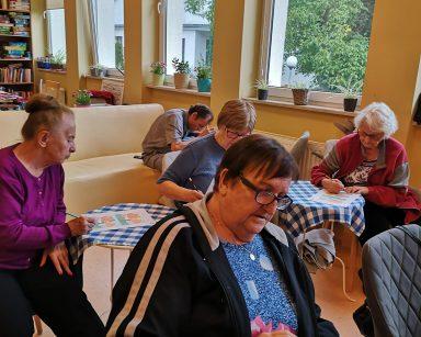 Seniorzy przy stolikach. Rozwiązują ćwiczenia na kartkach.