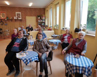 Zajęcia w sali Dziennego Domu Pobytu. Seniorzy siedzą przy stolikach.