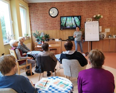 Terapeutka Małgorzata Jancelewicz prowadzi zajęcia. Przed nią, przy stolikach siedzą seniorzy. Na ekranie telewizora las.