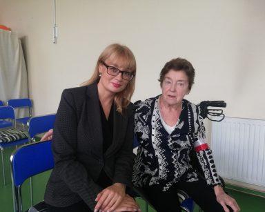 Obok siebie siedzą dyrektorka Agnieszka Cysewska i seniorka. Seniorka ma na ramieniu biało-czerwoną opaskę.