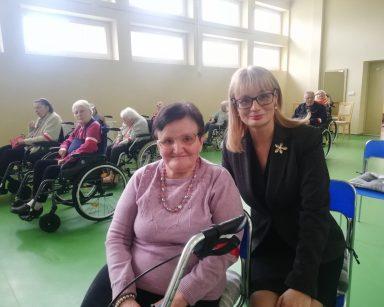 Na sali dyrektorka Agnieszka Cysewska i seniorka. Seniorka ma na ramieniu biało-czerwoną opaskę. W tle inni seniorzy.