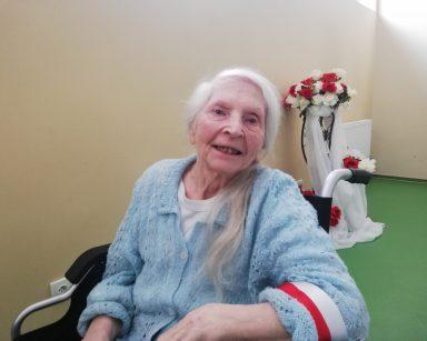 Uśmiechnięta seniorka z biało-czerwoną opaska na ramieniu. Za nią dekoracja z białych i czerwonych róż.