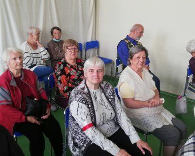 Na sali siedzą seniorzy. Część ma na ramieniu biało-czerwone opaski.