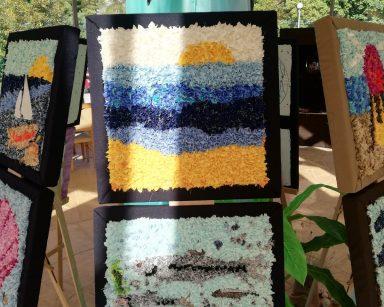 Ogród zimowy. Na sztalugach obrazy o tematyce morskiej wykonane z tkanin. Nad nimi dekoracja, kolorowe rybki z materiału.