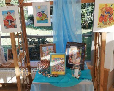 Udekorowana niebieskim materiałem pergola. Na niej oprawione rysunki. Na stoliku trzy rysunki w ramkach, rozłożone muszle.