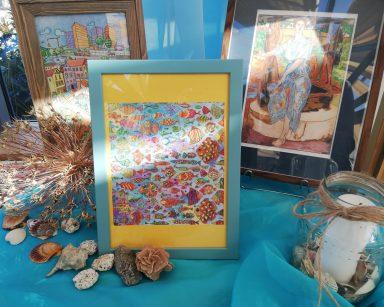 Na niebieskim materiale trzy kolorowe rysunki w ramkach. Obok rozłożone muszle i kamyki, świeczka w szklanym lampionie.