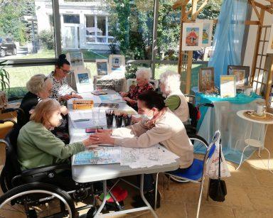 Seniorki, wolontariuszka, terapeutka Magdalena Poraj-Górska pracują nad rysunkami przy stole. Na blacie rysunki, kredki.