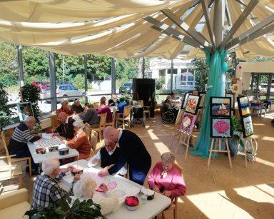Seniorzy, wolontariusze i pracownicy podczas warsztatów plastycznych w ogrodzie zimowym. Na środku wystawa prac.