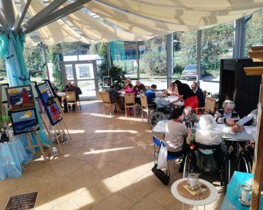 Seniorzy, wolontariusze i pracownicy przy stołach w ogrodzie zimowym. Na środku wystawa prac na sztalugach.