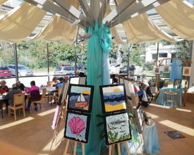 Ogród zimowy. Na sztalugach wystawa obrazów o tematyce morskiej. Przy stolikach seniorzy, wolontariusze i pracownicy.