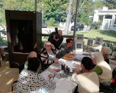 Seniorzy i pracownicy pracują przy stole nad obrazkami. Wolontariusz Andrzej Zięba robi zdjęcia. Obok tężnia solankowa.