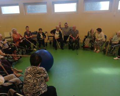 Seniorzy i seniorzy siedzą w kręgu. Drewnianymi kijkami odpychają niebiską piłkę.