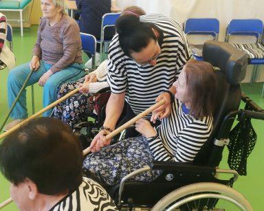 Seniorki siedzą na krzesłach. Każda trzyma drewniany kij. Terapeutka Magdalena Poraj-Górska pochyla się nad jedną z seniorek.