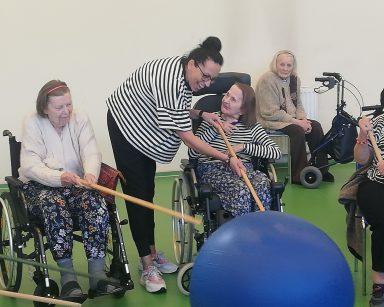 Seniorki drewnianymi kijkami odpychają niebiską piłkę. Terapeutka Magdalena Poraj-Górska pomaga jednej z seniorek.