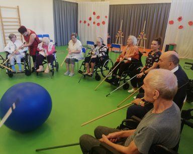 Seniorzy, koordynatorka Edyta Życzyńska, fizjoterapeutka Martyna Józefczyk. Bawią się odpychając kijkami niebiską piłkę.