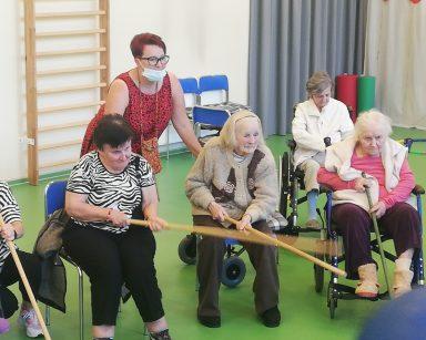 Seniorki bawią się wspólnie. Odpychają niebieską piłkę kijkami. Za nimi koordynatorka wolontariatu Edyta Życzyńska.