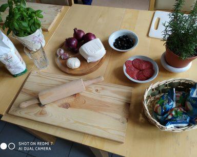 Na blacie mąka, mozzarella, czerwona cebula, salami, czarne oliwki, czosnek, zioła w doniczkach, drewniana deska i wałek.