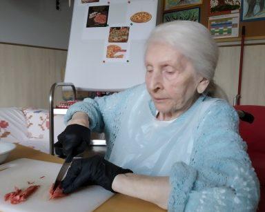 Przy stole seniorka. Kroi w paseczki plasterki salami. Za nią tablica ze zdjęciami pizzy.