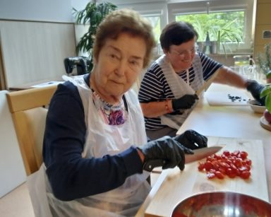 Przy stole dwie roześmiane seniorki. Pierwsza kroi pomidorki, a druga oliwki.
