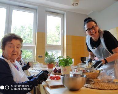 Przy stole dwie seniorki kroją pomidorki i oliwki. Na przeciwko roześmiana terapeutka Magdalena Poraj-Górska. Ugniata ciasto.