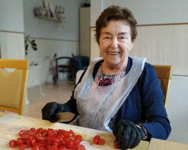 Seniorka kroi pomidorki na drewnianej desce. Uśmiecha się szeroko.