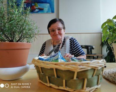 Uśmiechnięta seniorka przy stole. Przed nią koszyk z mozzarellą i doniczki z ziołami.