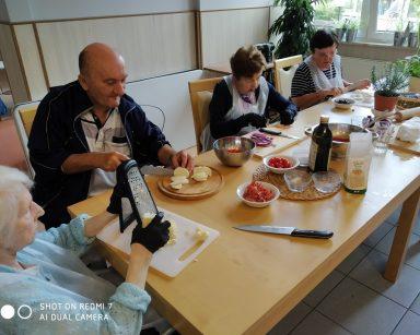 Przy stole czworo seniorów. Kroją i ścierają na tarce ser. Na blacie doniczki z ziołami, składniki do pizzy, oliwa.
