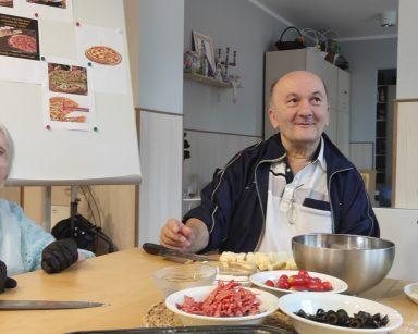 Dwoje seniorów przy stole. Na blacie pokrojone składniki na pizzę, pomidorki, starty ser.