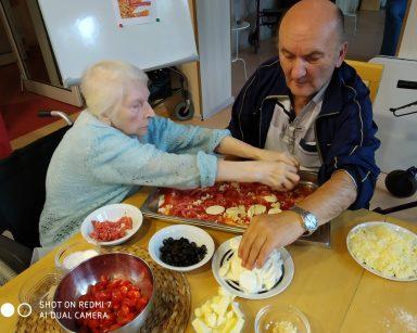 Dwoje seniorów wykańcza pizzę w prostokątnej blaszce. Układają na niej ser, pomidorki, oliwki, salami.