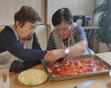 Dwie seniorki posypują startym serem pizzę w prostokątnej blaszce.