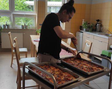 Dwie prostokątne blaszki z upieczoną pizzą. Terapeutka Magdalena Poraj-Górska odchyla łopatką brzegi ciasta od blachy.