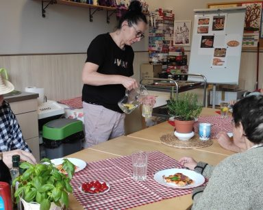 Wokół stołu, przy pizzy siedzą seniorzy, kierownik Arkadiusz Wanat. Terapeutka Magdalena Poraj-Górska nalewa wodę do szklanki.