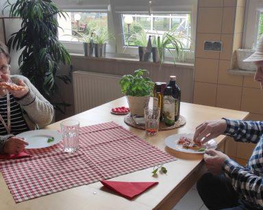 Przy stole na przeciwko siebie senior i seniorka. Jedzą pizzę. Na blacie serwetki w biało-czerwoną kratkę, doniczki z ziołami.