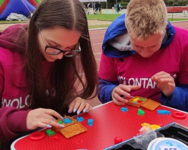Na stadionie Leśnym w Sopocie wolontariusze. Mają jednakowe różowe bluzy. Siedzą przy stoliku i grają w gry logiczne.