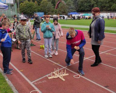 Stadion Leśny w Sopocie. Koordynatorka Edyta Życzyńska i wolontariusz grają z dziećmi w ringo. W tle inni uczestnicy festynu.