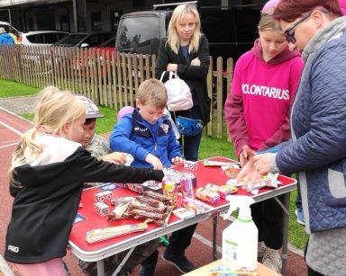Przy stoliku ze słodyczami troje dzieci, wolontariusze, koordynatorka wolontariatu Edyta Życzyńska.