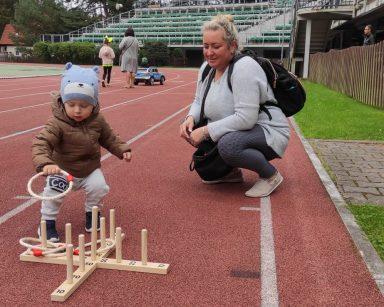 Mały chłopiec gra w ringo na stadionie. Obok niego kuca kobieta.