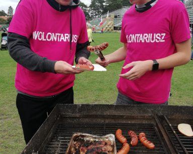 Dwaj wolontariusze stoją przy grillu. Nakładają na tackę upieczone kiełbaski.