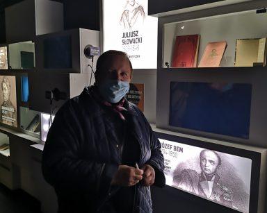 Seniorka zwiedza Muzeum Emigracji w Gdyni. Wystawa dotycząca sławnych Polaków miedzy innymi Mickiewicza, Słowackiego, Bema.