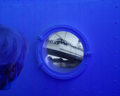 Seniorka w oświetlonym na niebiesko pokoju. Patrzy przez bulaj na biało-czarne zdjęcie statku.