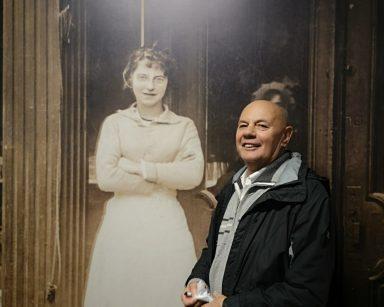 Senior stoi przy ścianie. Na ścianie zdjęcie kobiety w rzeczywistym rozmiarze.