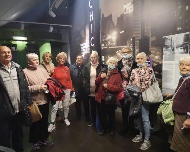 Muzeum Emigracji w Gdyni. Terapeutka Beata Brzozowska, wolontariuszka i seniorzy na zdjęciu grupowym.