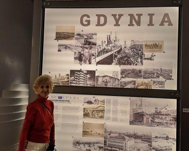 Seniorka przy wystawie poświęconej Gdyni. Na tablicach napis